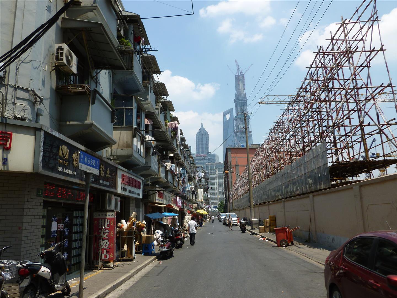 Typisches Stadtbild für Shanghai. Vorne kleine und bevölkerte Seitenstraße, im Hintergrund die höchsten Gebäude der Stadt.